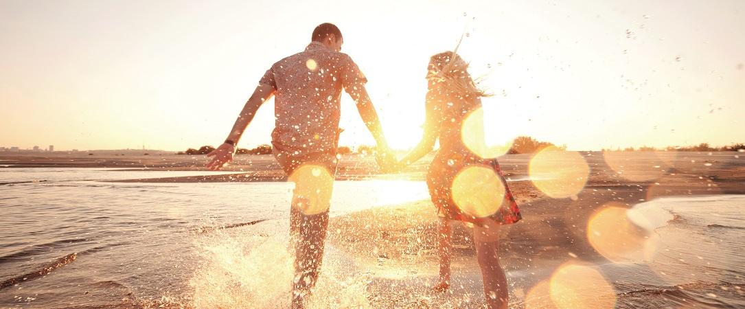 Couple on the beach into sunset