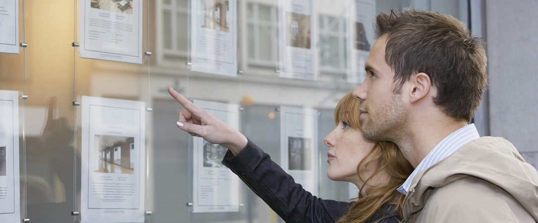Couple looking at real estate display window